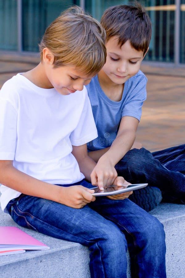 Twee kleine jongens die met tabletpc spelen, in openlucht stock foto's