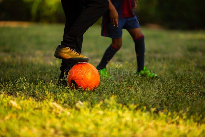 Twee kleine jongens die pret hebben die een voetbalspel op zonnige de zomerdag spelen royalty-vrije stock afbeelding