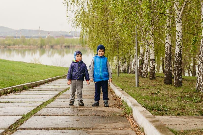 Twee kleine jongens die zich in het Park na de regen bevinden royalty-vrije stock foto's