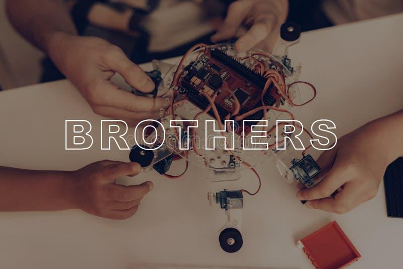 Twee Kleine Jongens en Jong Guy Robots Constructing stock afbeelding