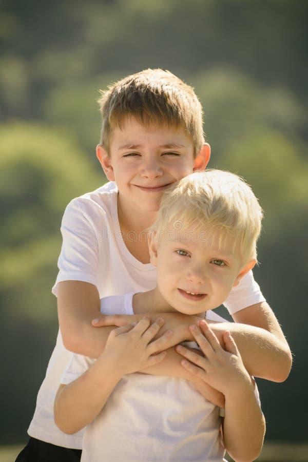 Twee kleine jongens koesteren in openlucht Concept vriendschap en broederlijkheid royalty-vrije stock afbeelding