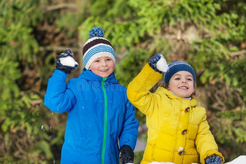 Twee kleine jongens met sneeuwballen in het park stock afbeelding