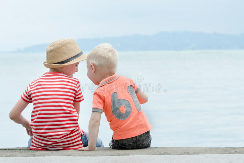 Twee kleine jongens zitten op een pijler, tegen het overzees en de bergen bedelaars stock afbeeldingen