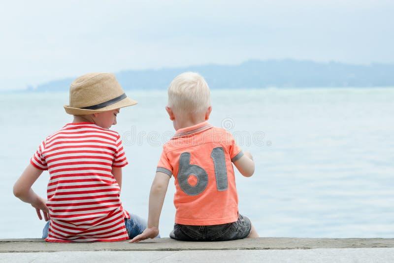 Twee kleine jongens zitten op een pijler, tegen het overzees en de bergen bedelaars royalty-vrije stock fotografie