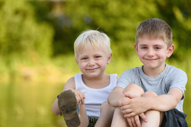 Twee kleine jongens zitten in openlucht Vage groene bomen in de afstand Concept vriendschap en broederlijkheid stock foto's