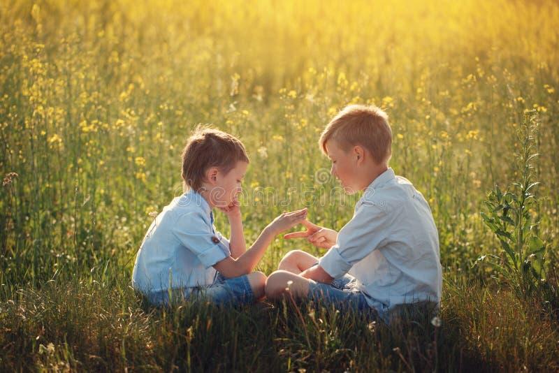 Twee kleine jongensvrienden die - steen, schaar, document spel in de zomerdag spelen stock afbeeldingen