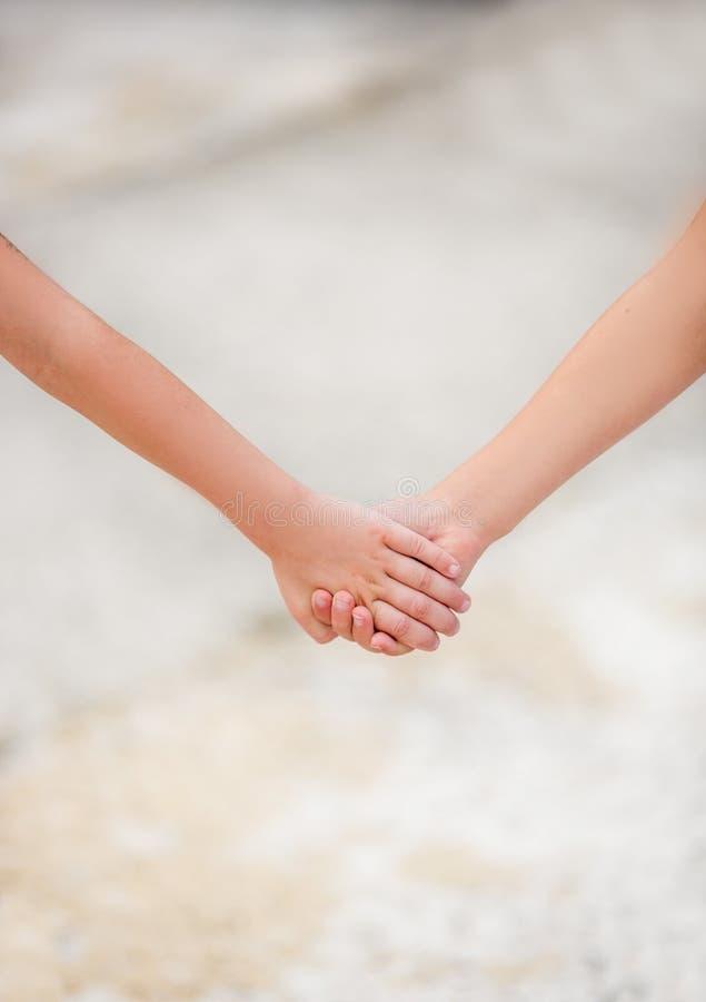 Twee kleine kinderen die handen houden Het concept vriendschap en liefde het helpen van kinderen en anderen stock fotografie