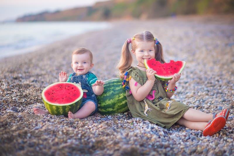 Twee kleine kinderen, jongensmeisje, die watermeloen op het strand eten, zomer die van mooie dag dicht bij oceaan genieten royalty-vrije stock foto's