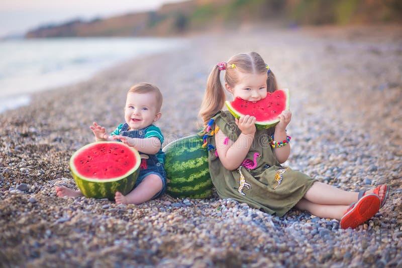 Twee kleine kinderen, jongensmeisje, die watermeloen op het strand eten, zomer die van mooie dag dicht bij oceaan genieten stock foto