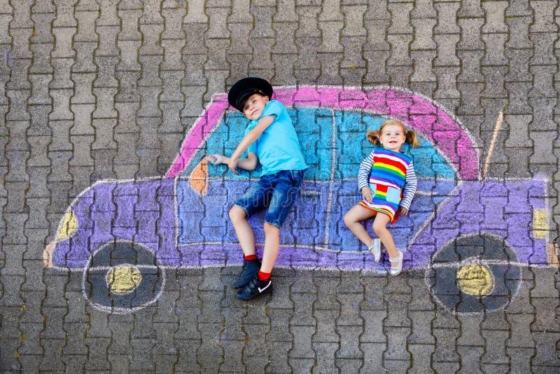 Twee kleine kinderen, knul en kleuter meisje, die plezier hebben met het tekenen van een auto-tekening met kleurrijke krijt op as vector illustratie