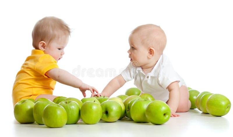 Twee kleine kinderen met groene appelen op wit stock foto