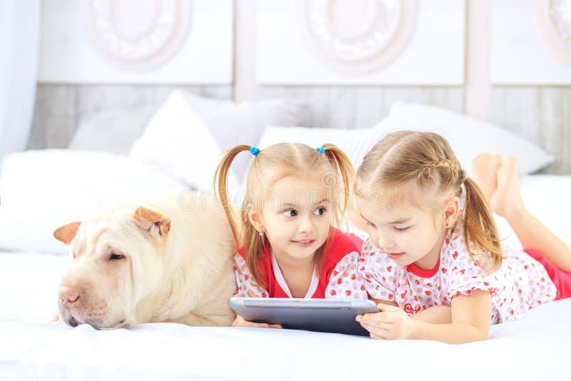 Twee kleine kinderenmeisjes die op beeldverhalen op de tablet letten Hond royalty-vrije stock foto