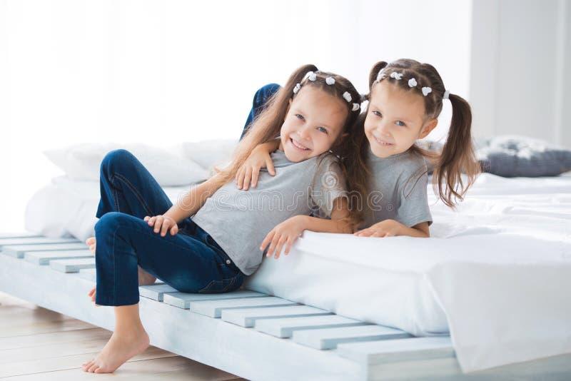 Twee kleine leuke het glimlachen tweelingen van meisjeszusters zitten op het bed in de ruimte stock afbeeldingen