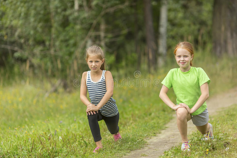 Twee kleine leuke meisjes die in openlucht opwarmen stock fotografie