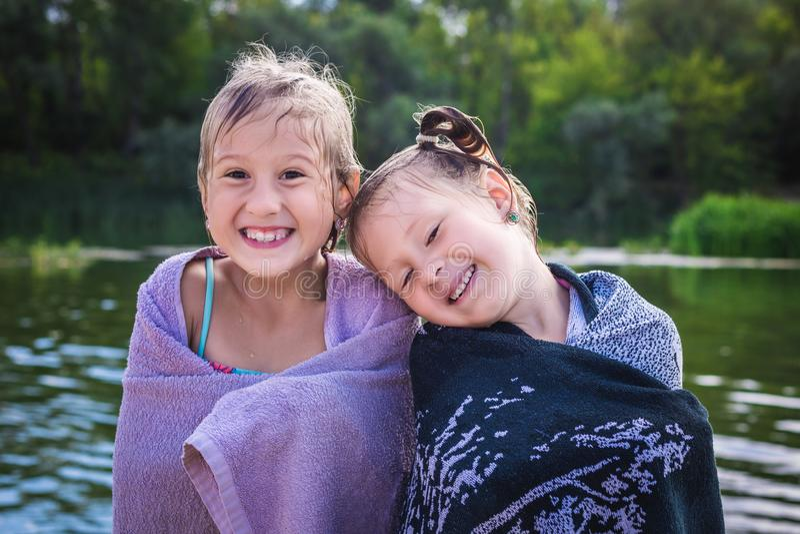 Twee kleine leuke meisjes op de kust van de vijver in handdoeken stock foto's