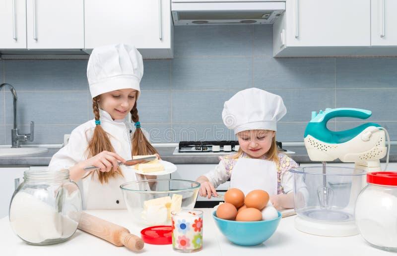 Twee kleine meisje-koks die boter voor deeg snijden royalty-vrije stock foto's