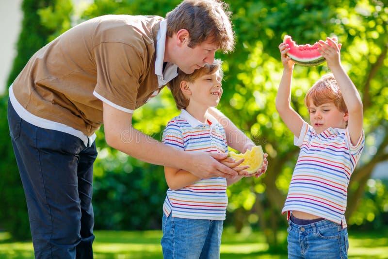 Twee kleine peuterjong geitjejongens en vader die watermeloen eten stock foto