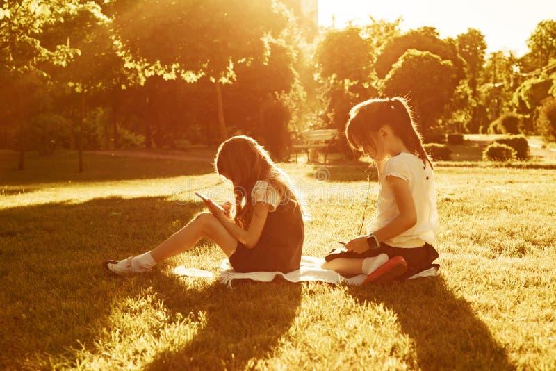 Twee kleine schoolmeisjes die een smartphone gebruiken Kinderen die, lezen, die de telefoon bekijken spelen, in het park, gouden  stock afbeeldingen