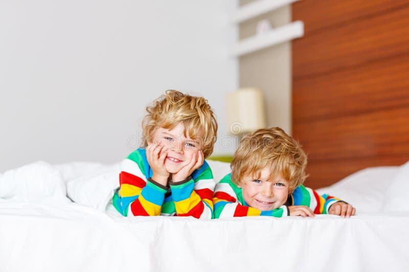 Twee kleine sibling jong geitjejongens die pret in bed na slaap hebben royalty-vrije stock afbeeldingen
