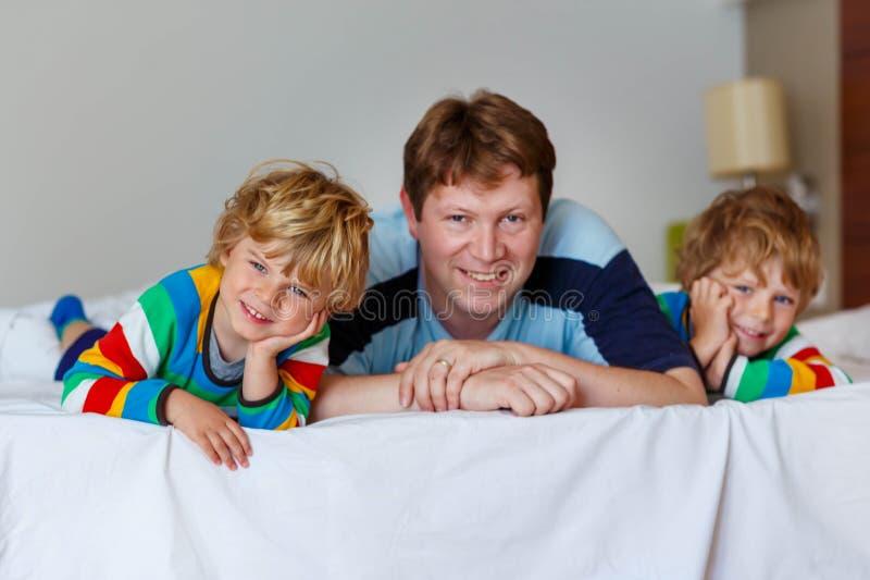 Twee kleine sibling jong geitjejongens en papa die pret in bed na slee hebben royalty-vrije stock afbeelding