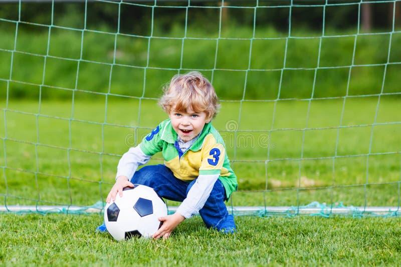 Twee kleine sibling jongens die voetbal en voetbal op gebied spelen stock fotografie