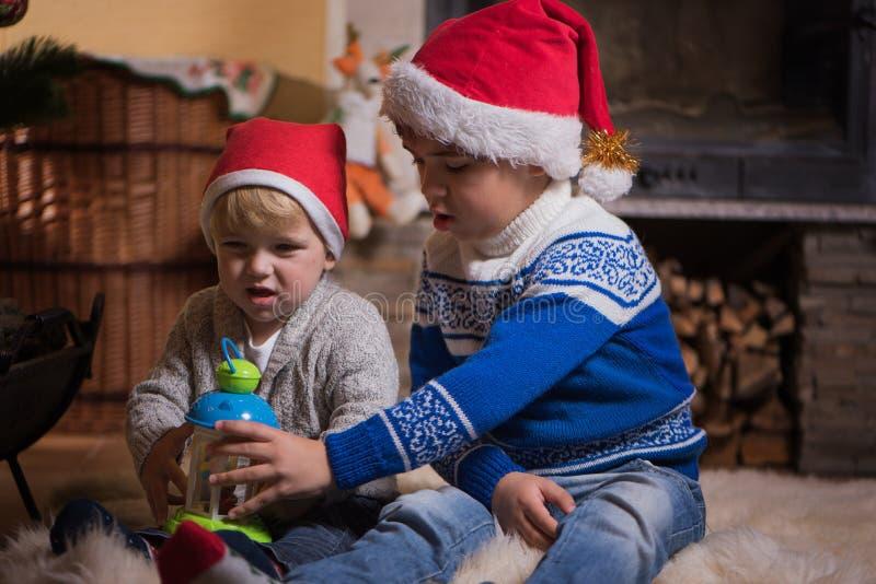 Twee kleine siblings die in santahoeden dichtbij open haard spelen stock foto's