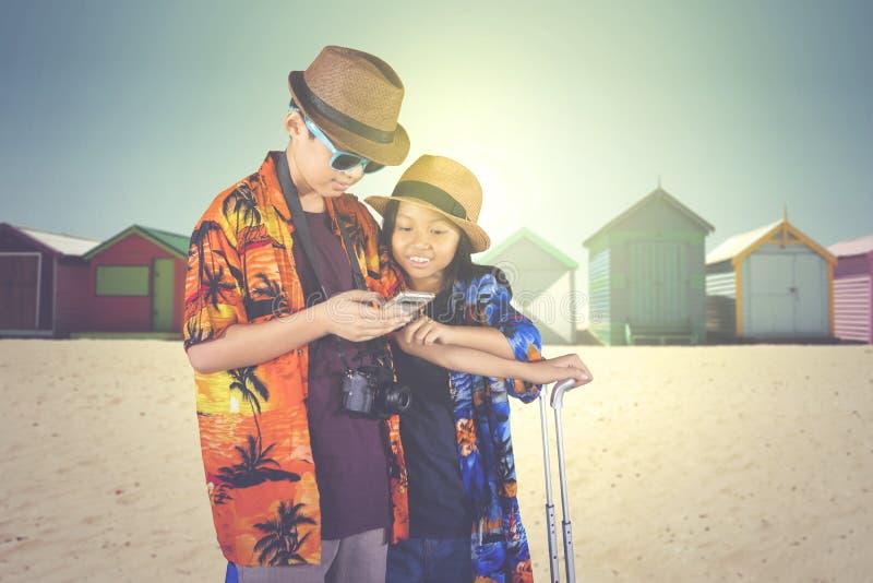 Twee kleine toeristen die een telefoon op het strand met behulp van stock afbeeldingen