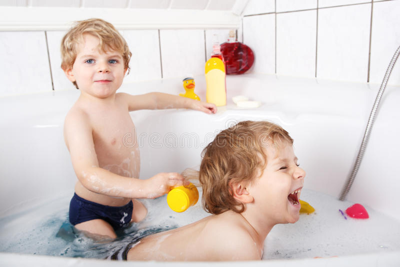 Twee kleine tweelingenjongens die pret met water hebben door bad in bedelaars te nemen stock foto