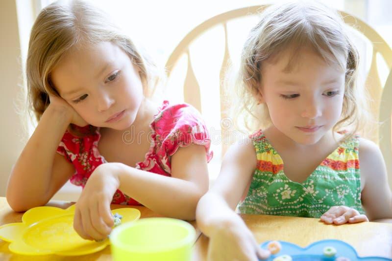 Twee kleine zustermeisjes die samen eten stock foto's