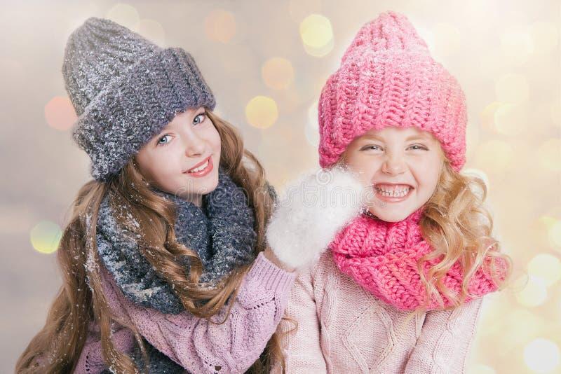Twee kleine zusters die in de winterkleren lachen Hoeden en sjaals Roze en grijs Familie De winter stock fotografie