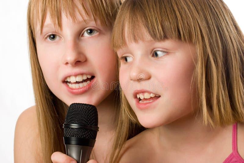 Twee kleine zusters die in microfoon zingen royalty-vrije stock afbeeldingen
