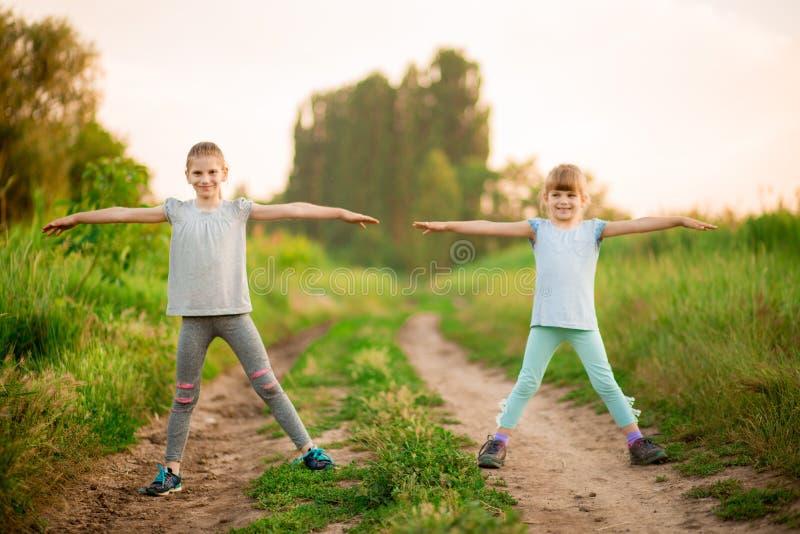 Twee kleine zusters die oefening in openlucht doen Gezonde Levensstijl royalty-vrije stock afbeeldingen