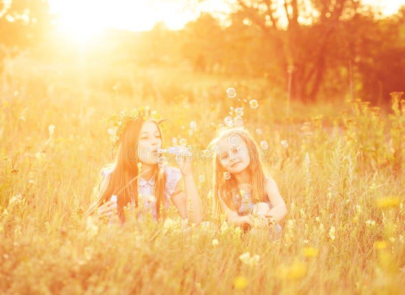 Twee kleine zusters die zeepbels blazen royalty-vrije stock afbeelding