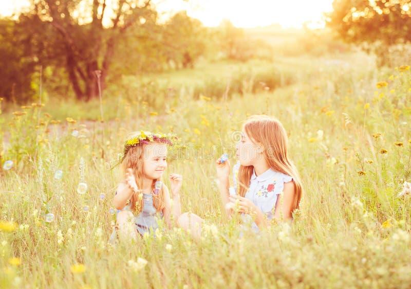 Twee kleine zusters die zeepbels blazen stock foto's