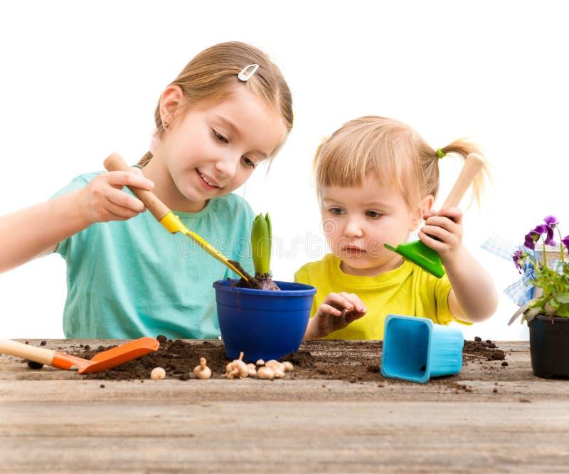Twee kleine zusters zijn bezig geweest met het tuinieren stock afbeeldingen