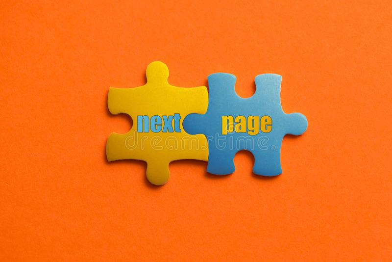 Twee kleurden details van raadsel met tekst Volgende Pagina op oranje achtergrond, Gele en Blauwe, dichte omhooggaand stock foto
