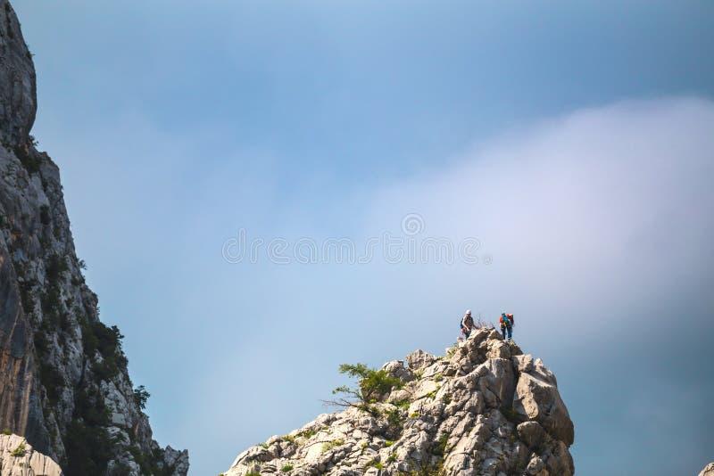 Twee klimmers beklimmen tot de bovenkant van de berg royalty-vrije stock afbeeldingen
