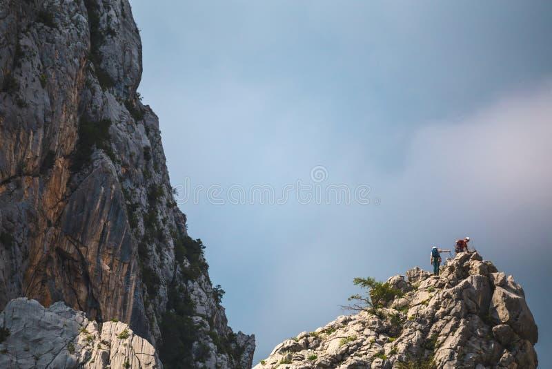Twee klimmers beklimmen tot de bovenkant van de berg royalty-vrije stock afbeelding