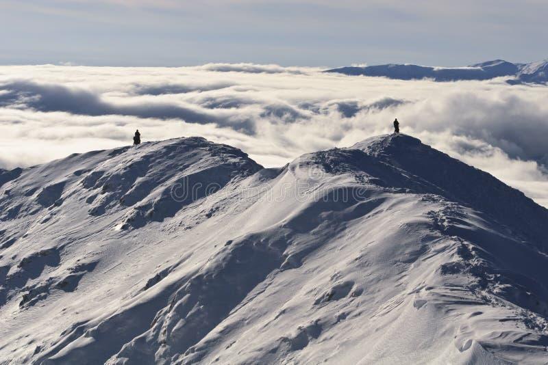 Twee klimmers op een bergbovenkant in de winter stock foto's