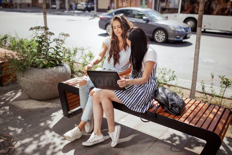 Twee knappe dunne meisjes met lang haar, gekleed in toevallige stijl, zitten op de bank en houden laptop op hun knieën royalty-vrije stock afbeeldingen