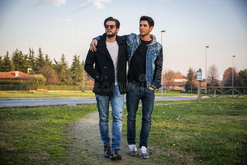 Twee knappe jonge mensen, vrienden, in een park stock fotografie