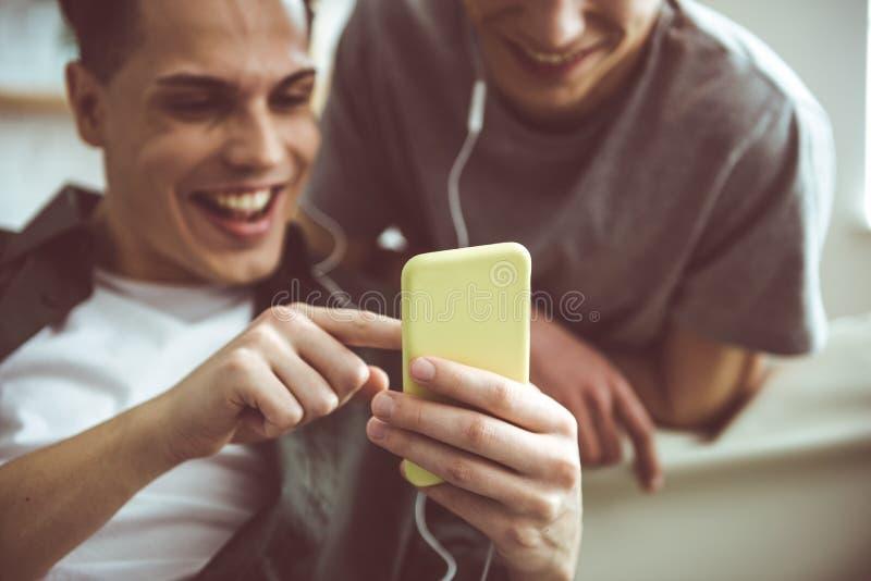 Twee knappe kerels die op video's bij smartphone en het glimlachen letten royalty-vrije stock afbeeldingen