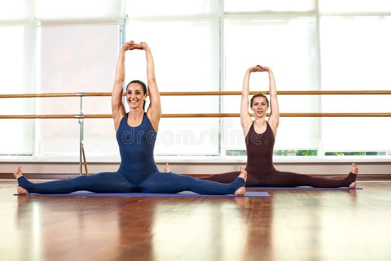 Twee knappe, slanke jonge vrouwen doen de yoga-pose terwijl ze in een glanzende gymzaal staan vlakbij een groot raam Begrip van royalty-vrije stock foto's