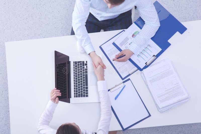 Twee knappe zakenlieden schudden hun handen, terwijl het werken in bureau royalty-vrije stock afbeelding
