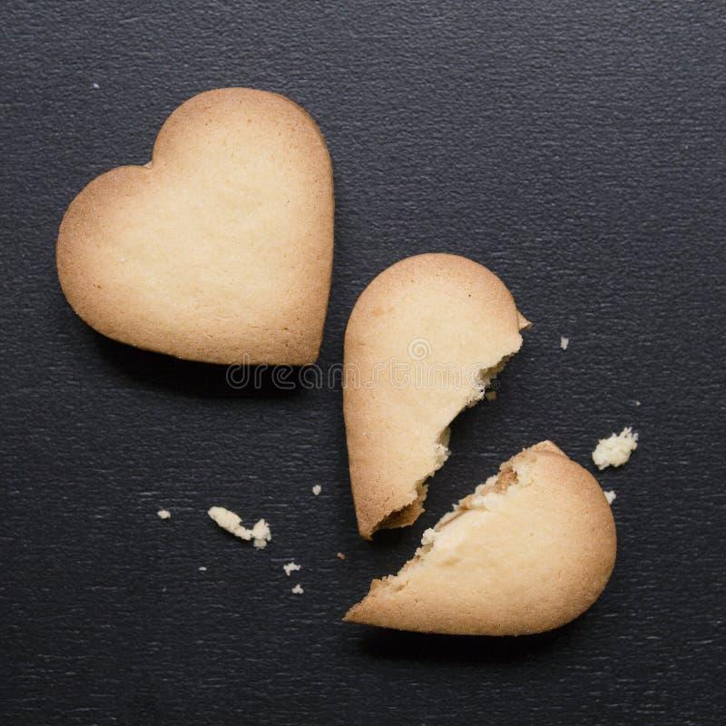 Twee koekjes in de vorm van hart, één van hen is gebroken op zwarte achtergrond Gebarsten hart gevormd koekje als concept verbrek royalty-vrije stock afbeeldingen