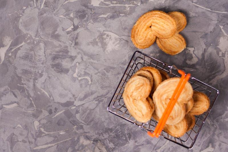 Twee koekjes in vorm van hart dichtbij partij van koekjes in metaal verchromen marktmand met oranje rubberhandvatten royalty-vrije stock fotografie