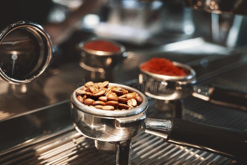 Twee koffiehouders met verse grondkoffie een andere met geroosterde bonen die op koffiemachine dicht opstaan stock afbeeldingen