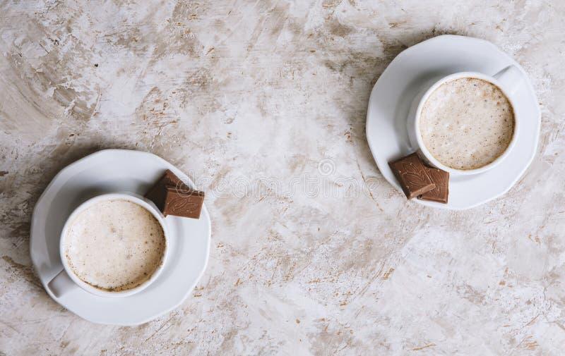 Twee koffiekoppen op een heldere uitstekende achtergrond stock afbeeldingen