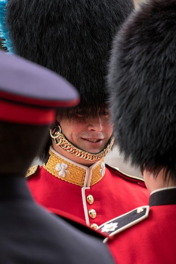 Twee Koninklijke Wachtmilitairen die een vriendschappelijk praatje hebben tijdens zich het Verzamelen de Kleuren militaire parade royalty-vrije stock afbeelding