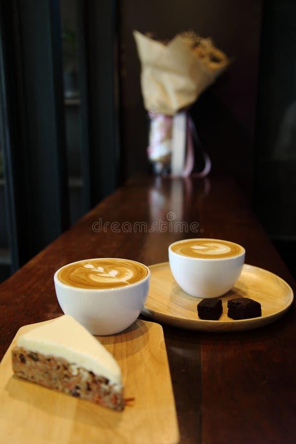 Twee kop van lattekoffie voor minnaar met de kunst van het tulpenpatroon op bovenkant met wortelcake en de brownie breken met exe stock foto